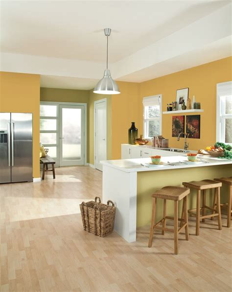 a kitchen dressed in sherwin williams yellow color of the month for september ceremonial gold