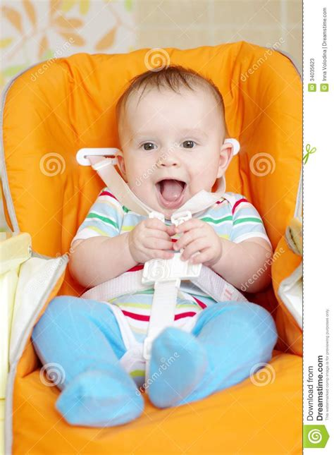 Laughing Baby Sitting On Babies Chair Age Of 6 Month Stock