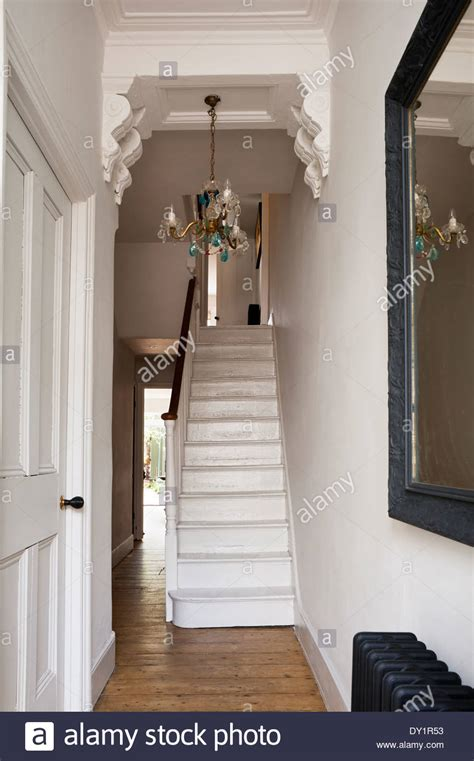 Chandelier In Hallway by White Wooden Staircase In Hallway With Corbels And Blue