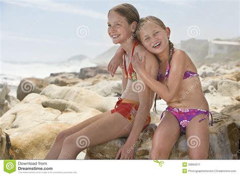 happy  girl sitting  sister  rocks stock image