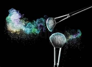 Two makeup brushes with powder on a black background ...
