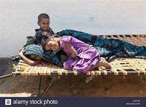 Indian village children playing on a bed outside their ...