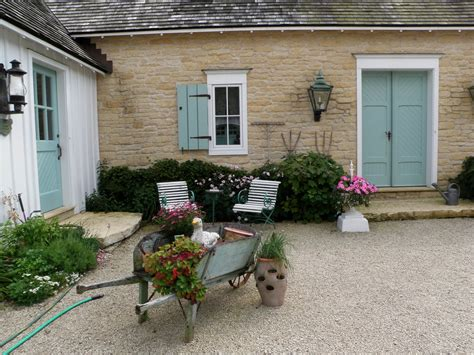 french country farmhouse courtyard with wheelbarrow hooked on houses