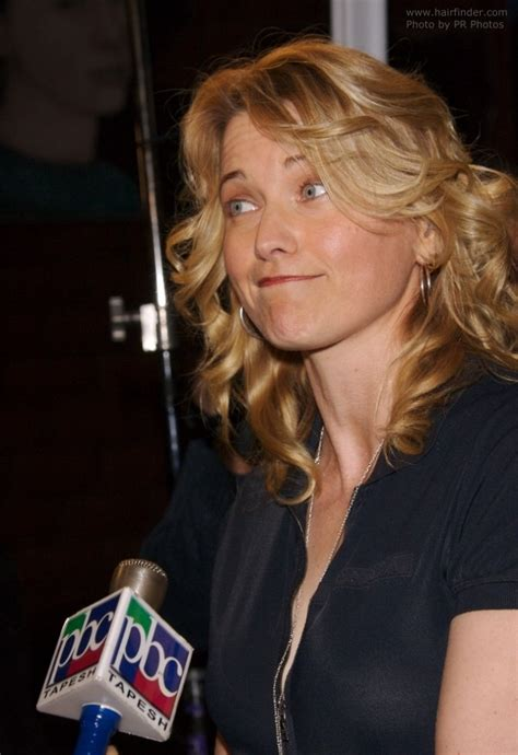 lucy lawless wearing long curly hairstyle  side bangs