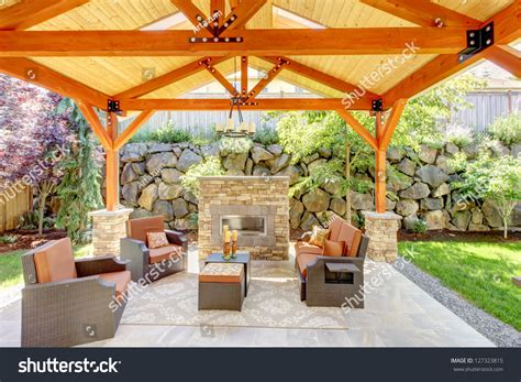 exterior covered patio with fireplace and furniture wood