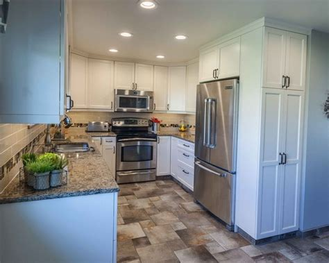 Black cabinets are an elegant option that feels way more glam than plain white. 4- Kitchen: Small, White Shaker Cabinets with Black Handles, Stainless Steel Appliances, Brown ...