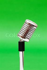 Vintage microphone against the bright green background ...