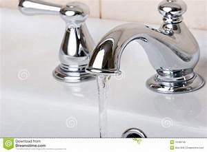 Silver chrome bathroom tap faucets running water stock for Is bathroom tap water drinking water