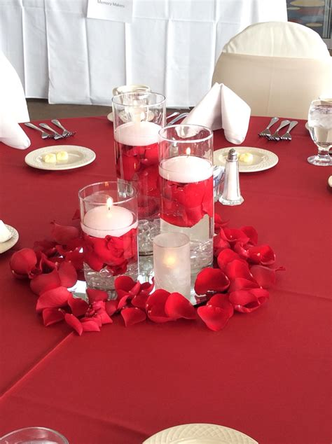 triple cylinder vases with floating candles and red rose
