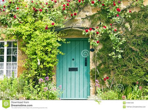 english cottage green doors  red roses stock photo