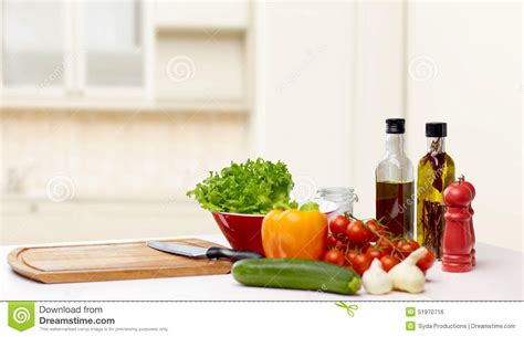 kitchen cuisine vegetables spices and kitchenware on table stock photo
