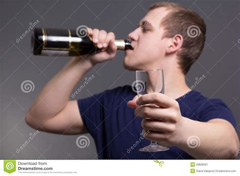 Young Man Drinking Alcohol Over Grey Background Stock