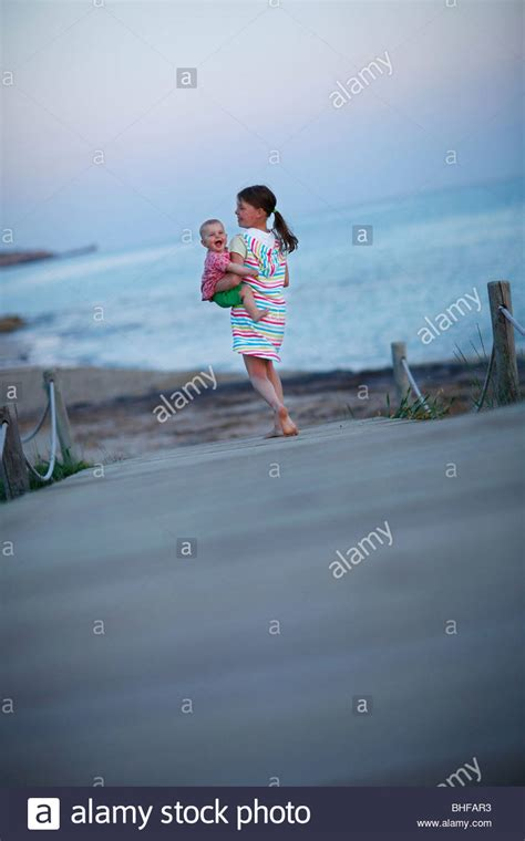 Girl Carrying Baby On Jetty Formentera Balearic Islands