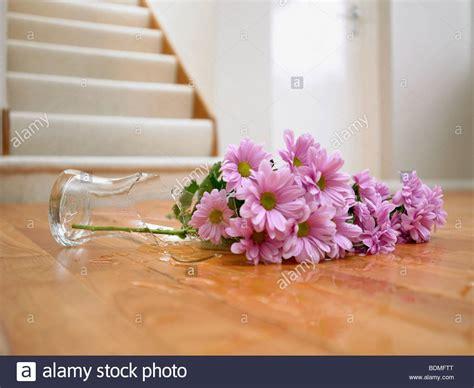 Broken Vase Of Flowers On Floor Stock Photo