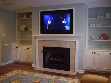 above tv square black fireplace with white shelf and tv above on