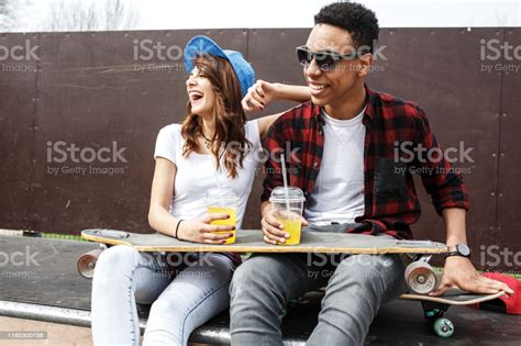 Young Teen Couple Sitting By The Wall And Hangout At The