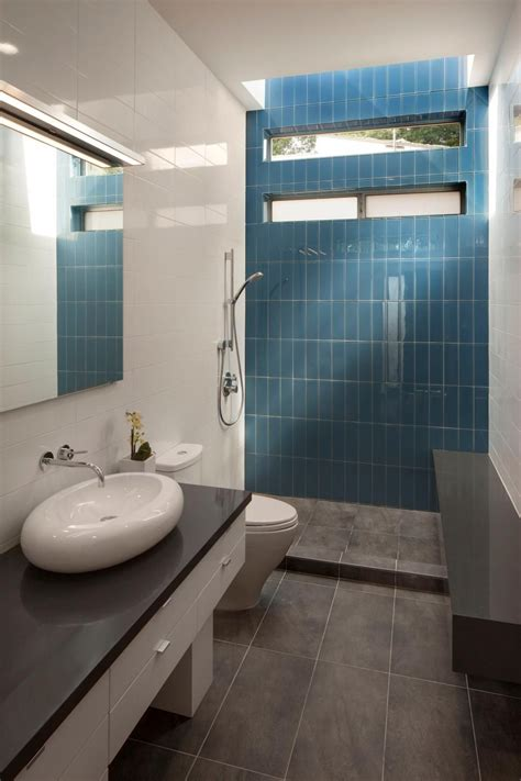 White Bathroom With Color Accents by A Bright Blue Tile Accent Wall At The Back Of The Shower