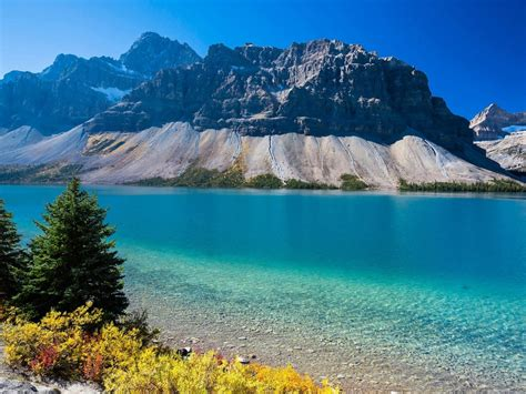 lake  clear blue water rocky mountains pine trees