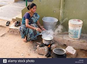 Indian woman cooking rice on an open fire outside her home ...