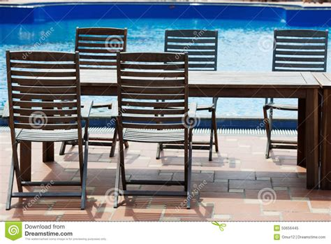 table and chairs on poolside stock photo image 50656445