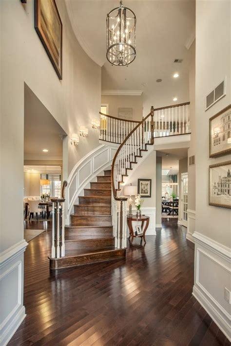 traditional entryway  wainscoting high ceiling chandelier dark hardwood floors wall