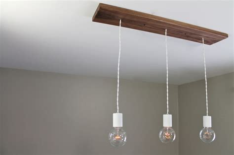 three bare bulb chandelier light fixture with wood canopy