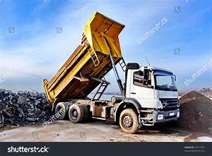 A Dump Truck Is Dumping Gravel On An Excavation Site Stock ...