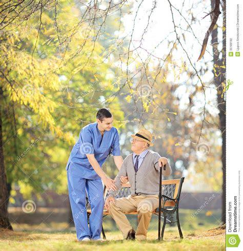 professionnel de soins de sant 233 parlant l homme sup 233 rieur assis sur l outsi de banc photographie