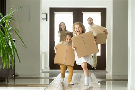 excited kids running holding boxes family moving   house stock photo  image