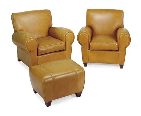 a pair of leather upholstered club chairs and ottoman