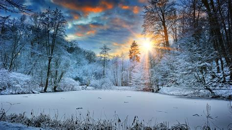 2048x1152 Sunbeams Landscape Snow In Winter Trees 4k