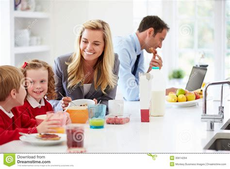 Family Having Breakfast In Kitchen Before School And Work Stock Images