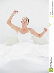 Cheerful woman yawning while stretching arms in bed