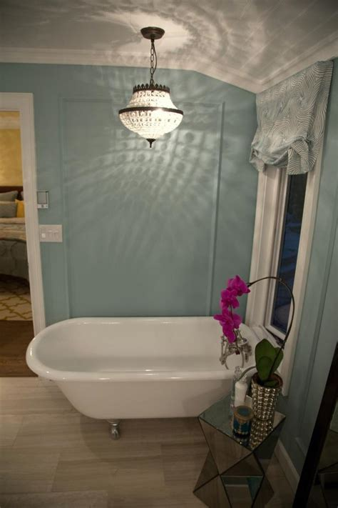 vintage style chandelier illuminates light blue bathroom