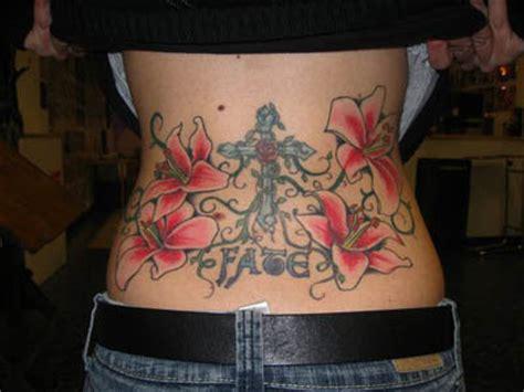 feminine flowers  cross tattoo  lowerback