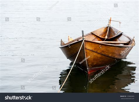 Row Boat On Water by Wooden Row Boat On Water Stock Photo 135883469