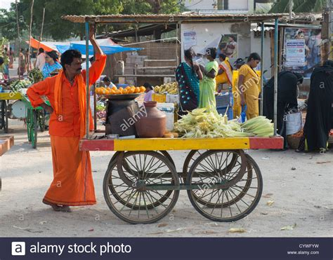 indian cart indian man street vendor selling cooked corn on the cob at
