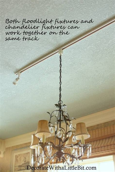 Chandelier hanging from track lighting fixture with
