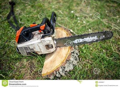 Professional Chainsaw On Pile Of Fresh Cut Wood Stock