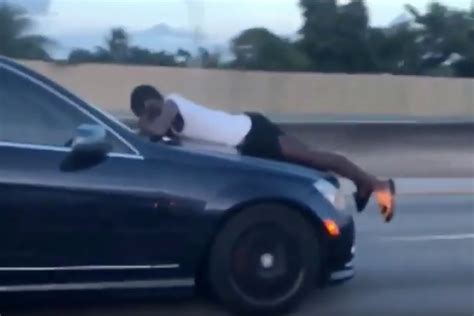 Man Talks On Phone While Riding On Hood Of Car Doing 70 Mph