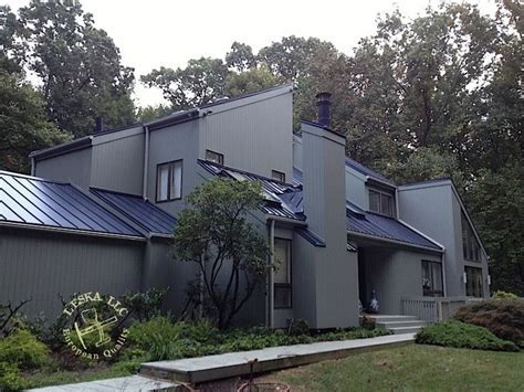 Gray monotone stucco with a single slop blue metal roof