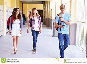 High School Students Walking In Hallway Using Mobile Phone ...