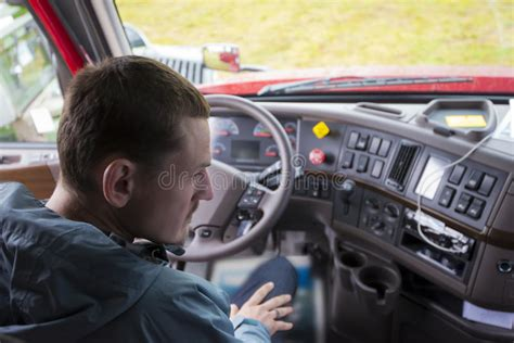 Truck Driver In Semi Truck Cab With Modern Dashboard Stock