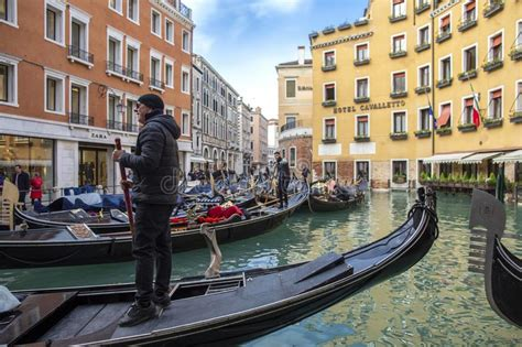 Venetian Gondolier Punting Gondola In Water Canal With
