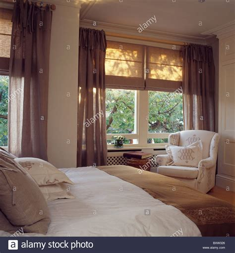 linen blinds and brown voile curtains on windows in