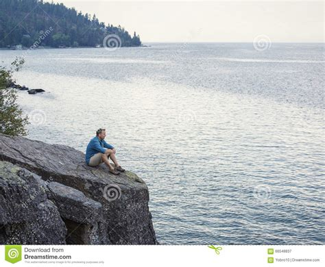 Perched On The Cliff Edge Overlooking The Sea by Meditating And Praying On Cliff Edge Overlooking