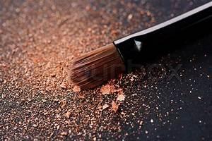 Powder scattered on black background from make up brush ...