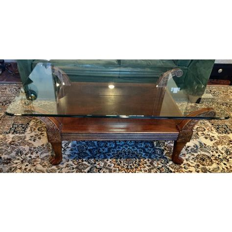 Try a mix of real wood in a finish like cherry or mahogany mixed with the airiness of a glass top. Carved Cherry Wood With Glass Top Coffee Table | Chairish