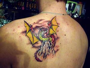 Awesome dragon with yellow wings which sits on a rock ...