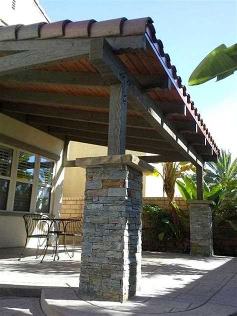 backyard patio cover design  stone pillars tile roof